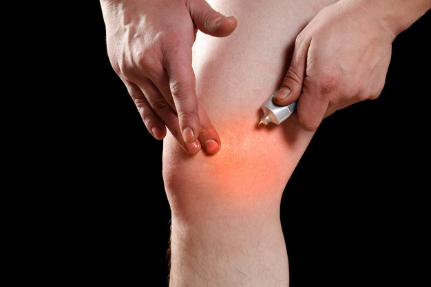 man rubbing ointment into affected knee 159057 720