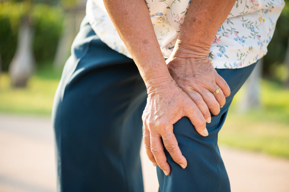 asian old woman walking park having knee pain knee injury park 1
